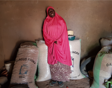 Amina in her store, surrounded by the bags of grain that she sells.