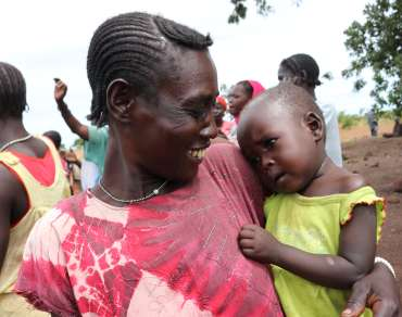 Mother in South Sudan holds and smiles at her infant child.