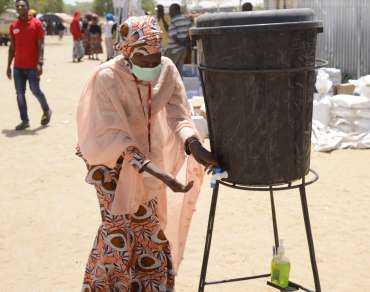 Bintu washes her hands in a camp in Nigeria