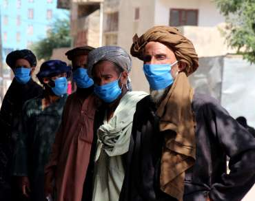 Men in afghanistan wearing face masks listen to coronavirus hygiene workshop