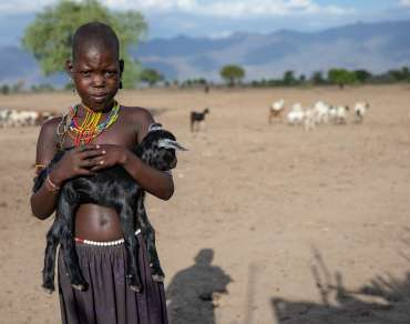 Young boy holds a goat in front of a parched, dry field.