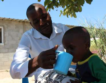 A father helps his young child drink from a cup outside a house