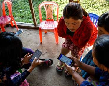 A group of women gather around a smart phone to view the Socialize to Immunize Facebook posts.