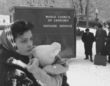 A woman holds a baby in the 1940s in front of a van saying 'World Council of Churches Refugee Service'.