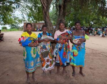 Four new mothers with their babies under a tree in Malawi