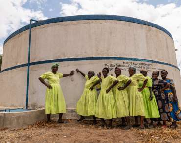 The climate advocacy group in Masue, Kenya, with the water tank built by the community.