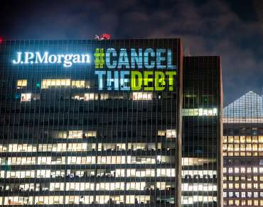 'Cancel the Debt' projected on the side of the JP Morgan Building