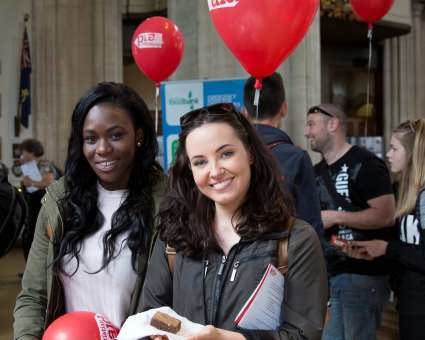 Two smiling women in church with Christian Aid balloons