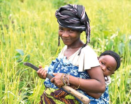 Jebbeh and baby, featured in Christian Aid Week, in a field.