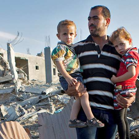 A man holding two children in his arms in Gaza. In the background there are buildings which have been redcued to rubble.