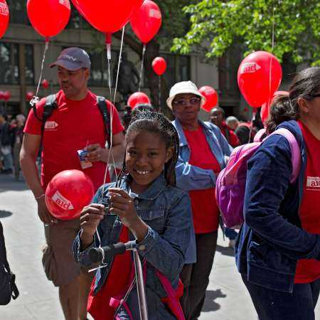 Girl holding Christian Aid balloons among a crowd of Christian Aid fundraisers
