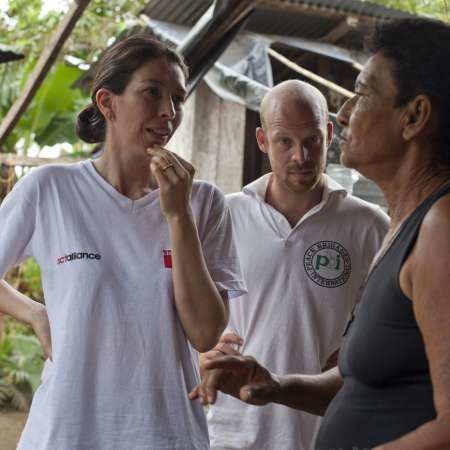 Christian Aid staff member in Act Alliance t-shirt talks to community member in Colombia