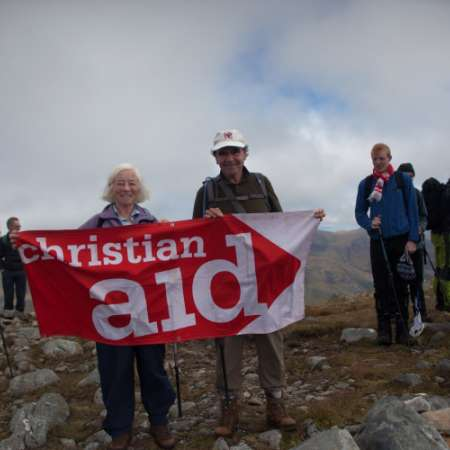 Christian Aid supporters on a mountain holding up a banner