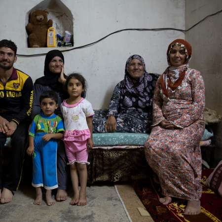 Ahmed sits with his family in temporary accommodation after fleeing Syria