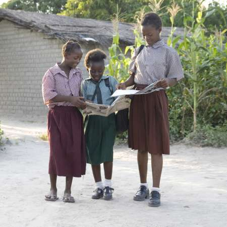 Three girls walking home from school whilst reading a book, Zambia