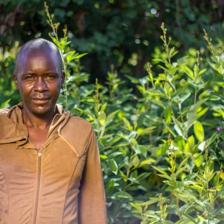 Richard Nyoni smiles at camera in front of green field of crops
