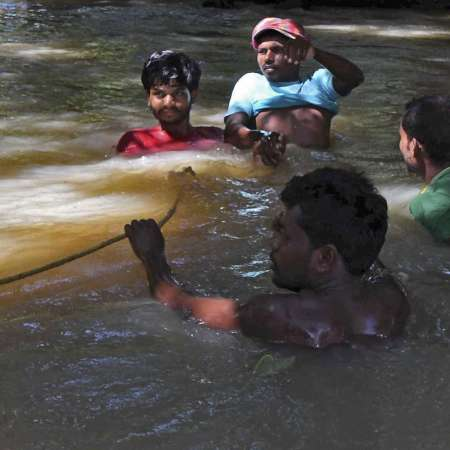 Men submerged in floodwater in South Asia