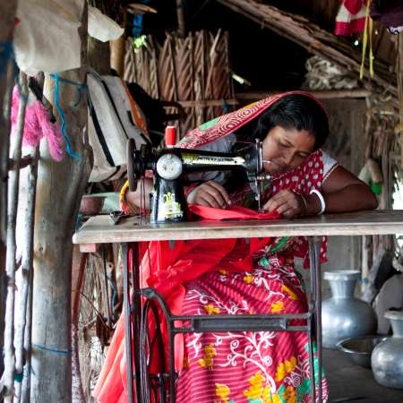 Ponchi Rani Mondol sits at her sewing machine at home in Bangladesh