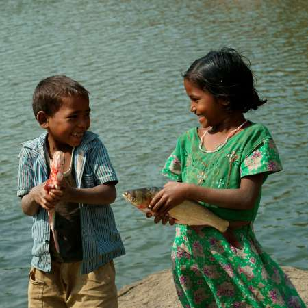 Two children holding fish and smiling with lake in background.