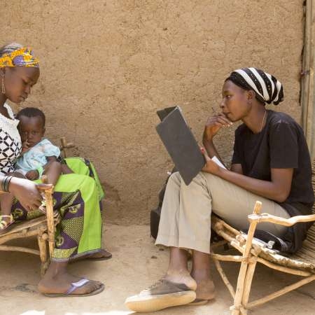 Baribsi village, Yako province, Burkina Faso. Sally Belem, 32, conducts a survey into child nutrition in the Yako area, part of a two year study. Here she interviews a mother as part of the BRACED programme.
