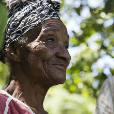 75 year old Etike Aubert stands on her land next to growing bananas