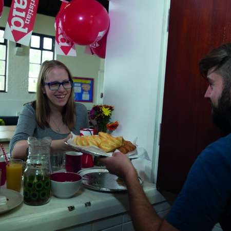 Woman serves man breakfast though a serving hatch
