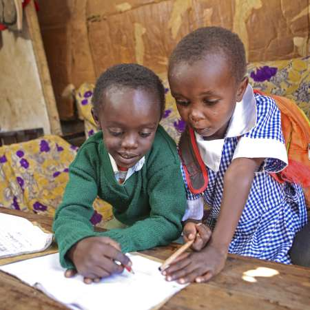 Two young children sit at a coffee table doing their homework in Kenya
