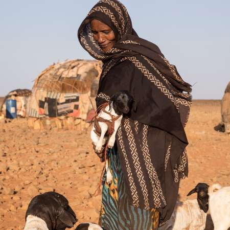 Dimma Gollo carries a goat in northern Kenya