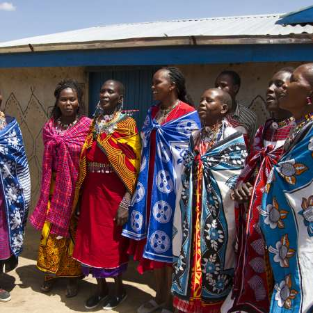 A group of women sing with members of different Mother to Mother groups outside a home in Narok West, Kenya.