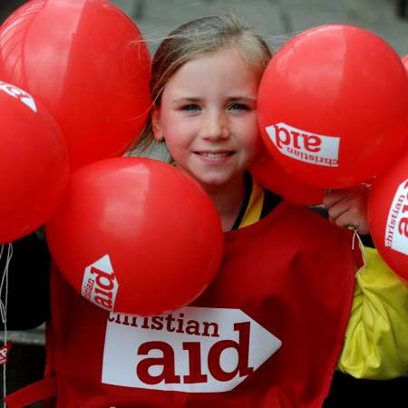 Girl holds balloons at a Christian Aid fundraising event