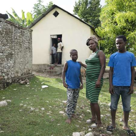 Vilia stands with her children in Haiti Christian Aid