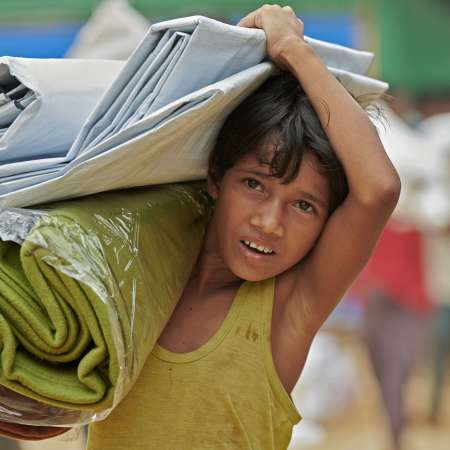 A Rohingya boy carries blankets at Jamtoli Refugee Camp
