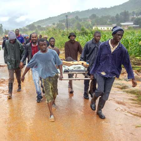 Group carry injured person on stretcher following Cyclone Idai