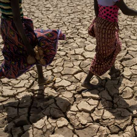Two women walk across the dry cracked earth of empty Louda dam in Burkina Faso